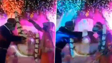 सोशल डिस्टेंसिंग का दूल्हा-दुल्हन ने निकाला गजब का जुगाड़, एक-दूसरे को ऐसे पहनाई वरमाला (Watch Viral Video)