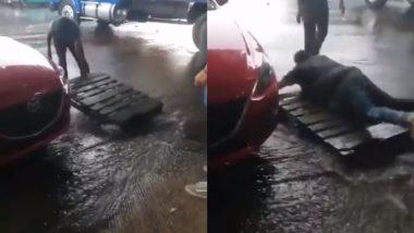 बारिश के पानी से बॉस को बचाने के लिए कर्मचारी ने सड़क पर लगाई तख्ती, उस पर कदम रखते ही मालिक गिरा धड़ाम (Watch Viral Video)